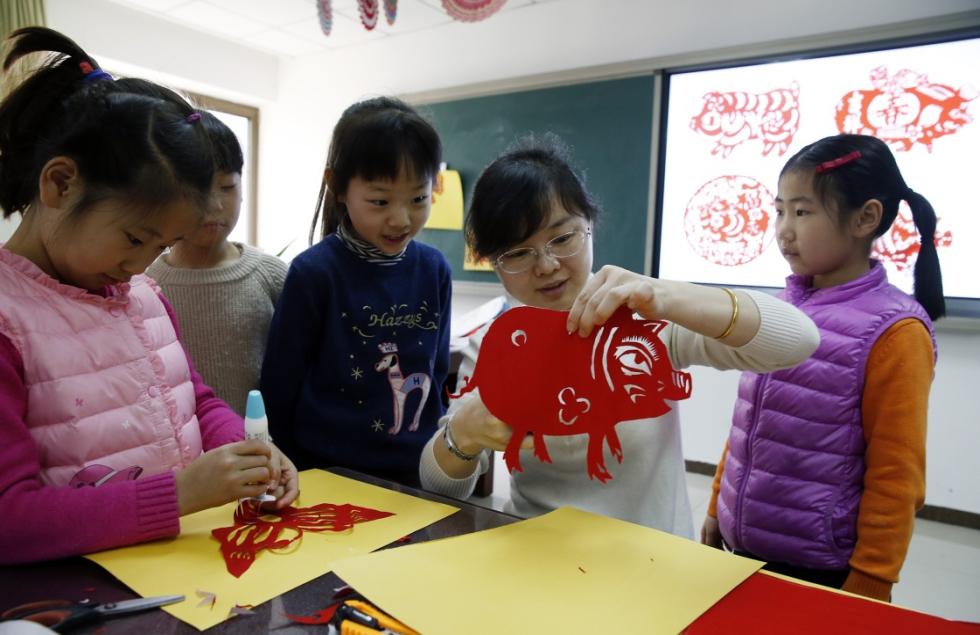1月12日,小学生在学习生肖猪剪纸制作.新华社发(周良摄)