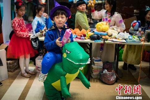"""騎著可愛""""小恐龍""""的孩子參加愛心義賣。 泱波 攝"""